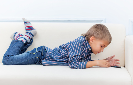 Boy is lying on the sofa and play with his smartphone