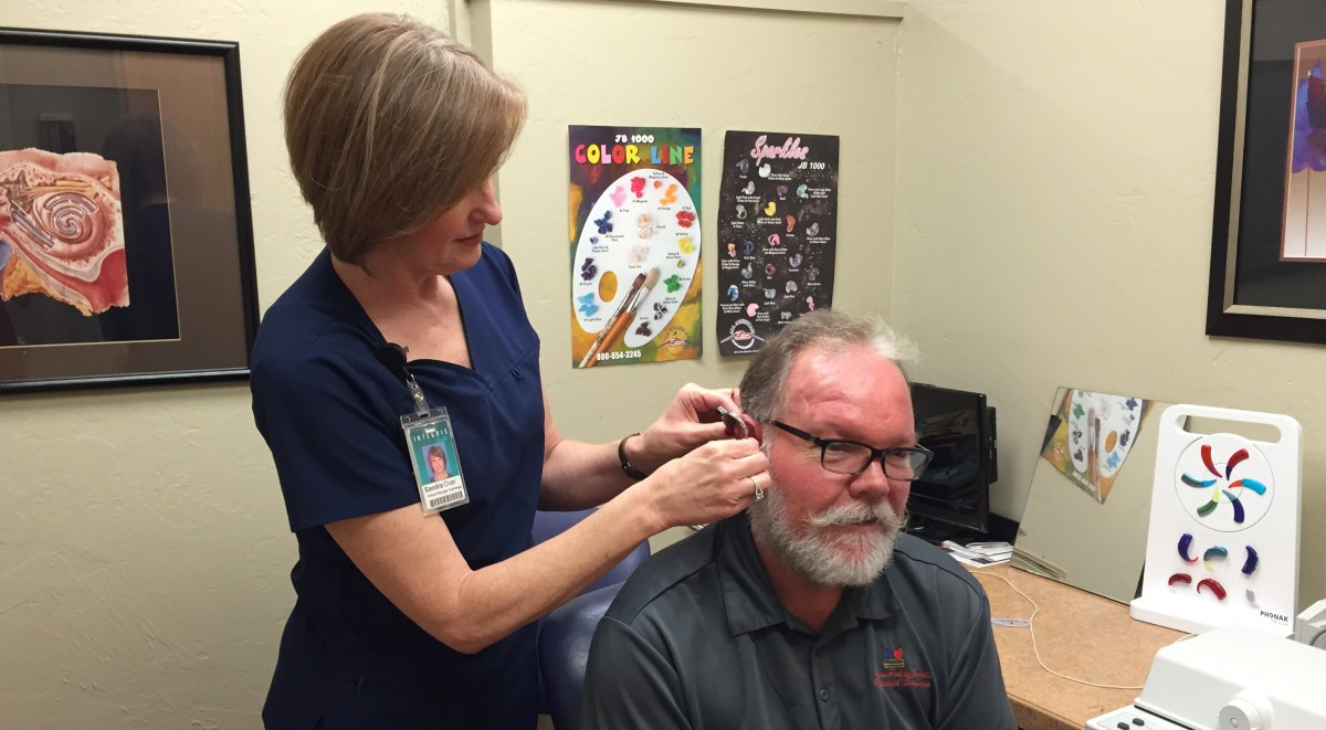 Woman doctor fitting a man for a hearing aide