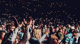 people applauding at a concert at night time holding lighters