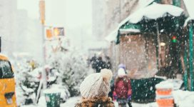 Girl crossing the street in a snow storm in the city wearing warm clothes
